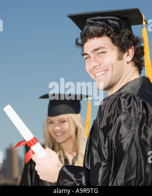 Man wearing graduation cap and gown with diploma - Stock Photo