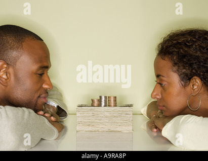 Couple looking at pile of money - Stock Photo