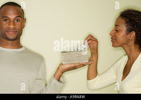 Woman taking money from stack in husband s hand - Stock Photo