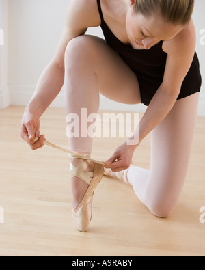 Female ballet dancer tying pointe shoes - Stock Photo