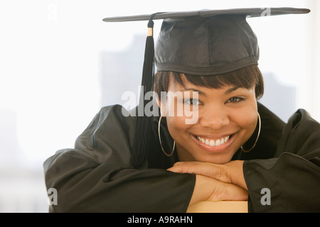 African woman wearing graduation cap and gown - Stock Photo