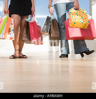 Two women carrying shopping bags - Stock Photo