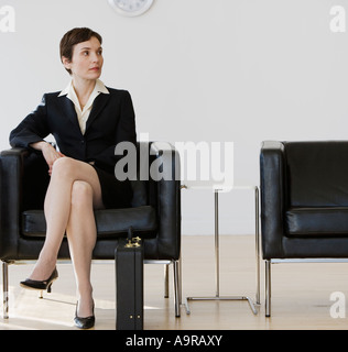 Businesswoman sitting in waiting area - Stock Photo