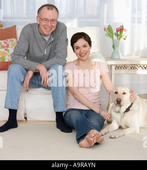 Portrait of couple with dog in livingroom - Stock Photo