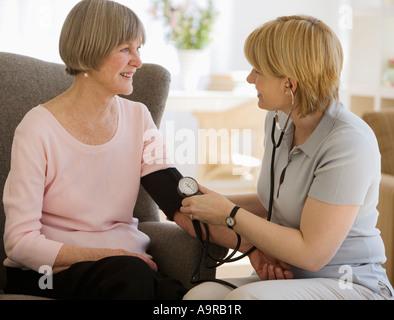 Senior woman having blood pressure taken - Stock Photo