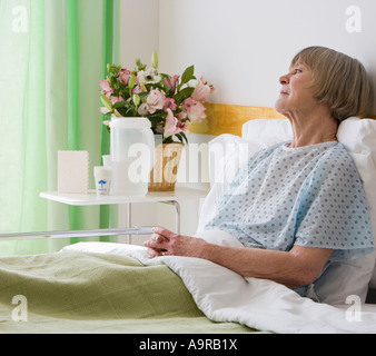 Senior woman laying in hospital bed - Stock Photo