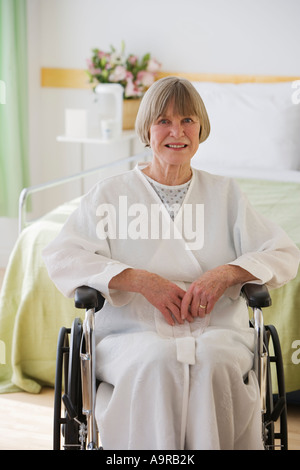 Senior woman sitting in wheelchair at hospital - Stock Photo