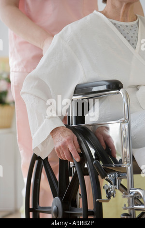 Nurse pushing senior woman in wheelchair - Stock Photo