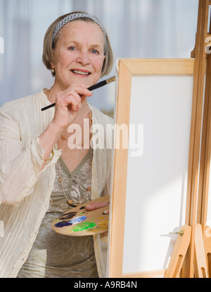 Senior woman painting on easel - Stock Photo