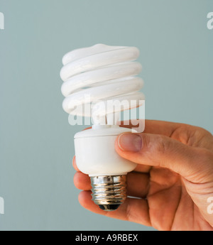 man holding energy efficient light bulb stock photo
