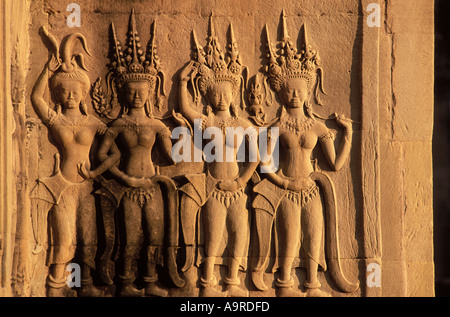 Carvings of apsaras celestial dancers who entertain the gods on a gallery wall at Angkor Wat Cambodia - Stock Photo