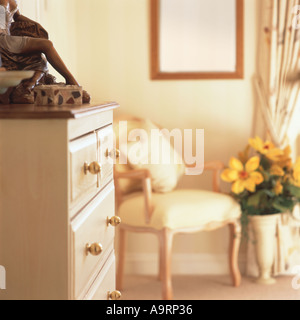 Modern bedroom image including the front of a chest of drawers with an elegant armchair and flowers in the background - Stock Photo