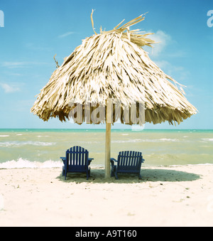 Two sun chairs under a palapa on a beach in Southern Belize - Stock Photo