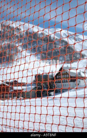 Mountain Chalet through orange netting - Stock Photo