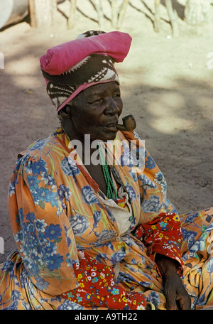 Herero woman wearing traditional clothes and headdress smoking a pipe - Stock Photo