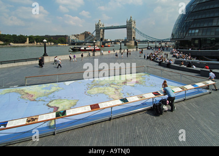 Riverside walkways at Greater London Authority City Hall by River Thames & Tower Bridge with world map display for - Stock Photo