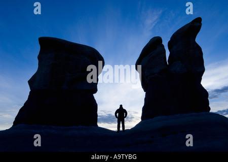 Man standing between two sandstone features in Devil's Garden Utah