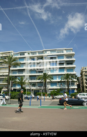 Pedestrians, rollerblader, jogger and 1950's apartment building on the Promenade des Anglais, Nice France - Stock Photo