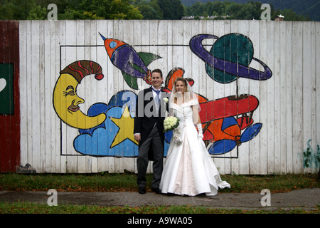 bride and groom in front of Graffiti wall painting - Stock Photo