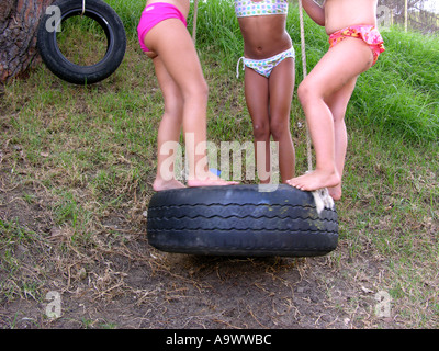 Three little girls standing together on a giant rubber tyre swing - Stock Photo