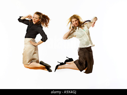 two lovely young women jumping in the air, one holding her glasses, the other with a mobile or cell phone to her - Stock Photo