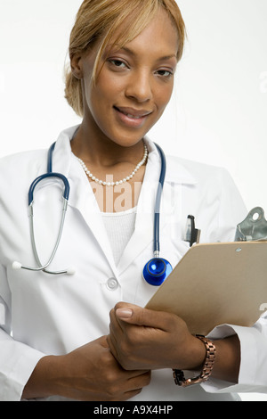 Young woman doctor in a white coat with a clipboard and stethoscope smiles at the camera - Stock Photo