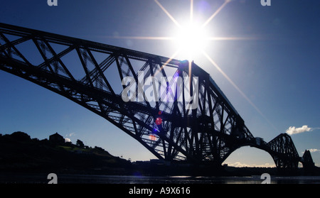 Silhouette of the Forth Rail Bridge with the sun directly obove taken from North Queensferry Fife Scotland - Stock Photo