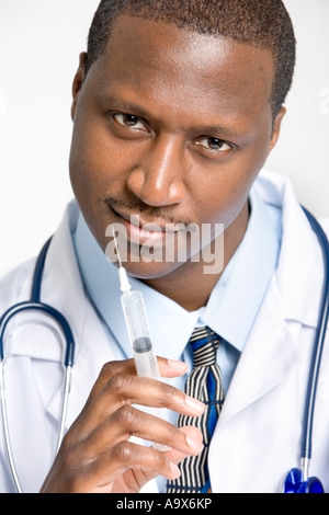 Young doctor with a syringe prepares to give the patient an injection while wearing a white coat - Stock Photo