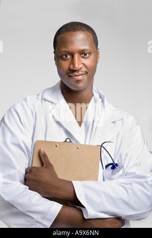 Young black doctor wearing a white coat and stethoscope holding a clipboard and smiling at the camera - Stock Photo