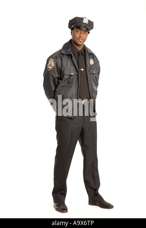 Black American police officer standing with his hands behind his back looking at the camera - Stock Photo