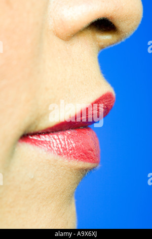 mouth and nose of a pretty woman wearing red lipstick on a blue back ground - Stock Photo