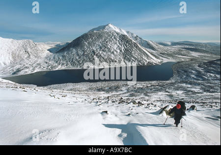 Mountain climbers are going up the Narodnaya Mount Slope The Polar Urals Russia Blue lake - Stock Photo