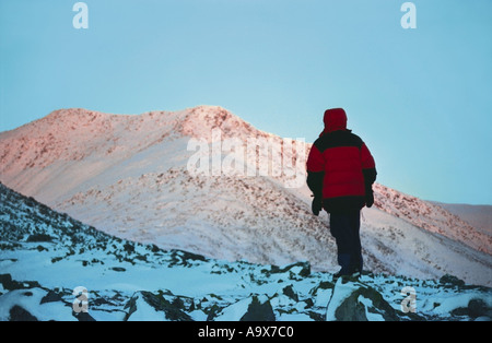 A mountain climber is standing in front of the highest peak of the Urals the Narodnaya Mount Sunrise The Polar Urals - Stock Photo