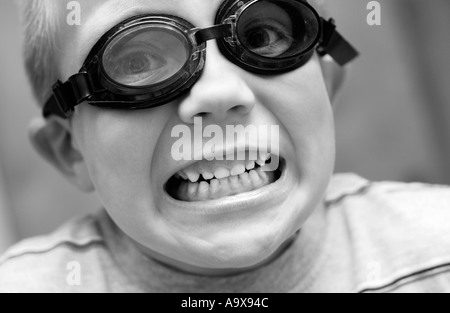 5 year old boy wearing goggles with mouth open - Stock Photo