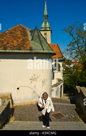 Woman walking up the steps to Bratislava castle with St Martins church in the background Slovakia EU - Stock Photo