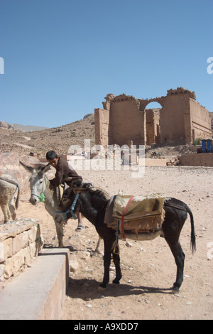 A boy and his donkeys in front of Qasr al-Bint, a Nabatean temple in Petra, Jordan. Jordan. - Stock Photo