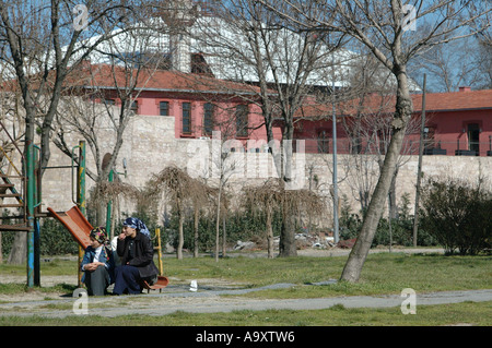 View of a children's playground in Istanbul, Turkey with 3 girls in headscarves, chatting - Stock Photo
