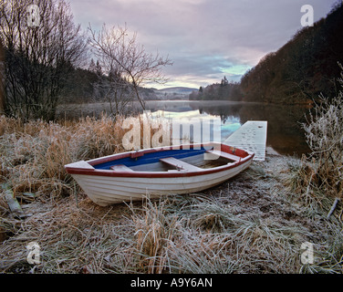 A small white row boat used for fishing is hauled out onto the shore of frosted Loch Ard, near Aberfoyle, Scotland. - Stock Photo