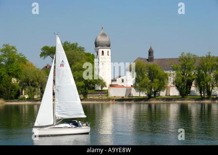 Sailboat and church tower of Frauenwoerth monastery Frauenchiemsee Fraueninsel Chiemsee Bavaria Germany - Stock Photo