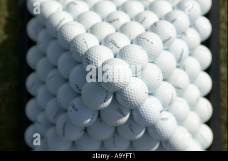Golf balls set up in a pyramid on a practice range. - Stock Photo