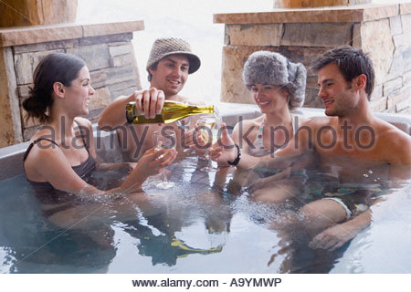 Friends having wine in hot tub - Stock Photo