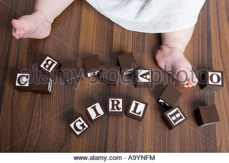 Baby girls feet and building blocks - Stock Photo