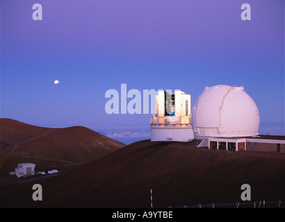 Subaru Telescope and Keck 1 Telescope in morning twilight with partially eclipse moon - Stock Photo