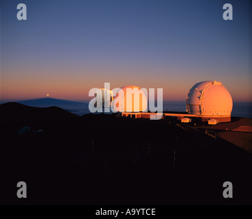 Twin Keck Telescopes with the partially eclipsed moon above the shadow of Mauna Kea - Stock Photo