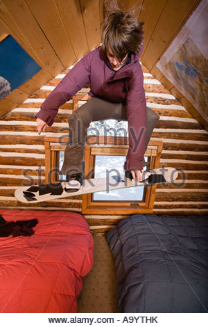Man snowboarding in chalet - Stock Photo