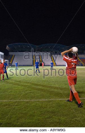 Footballer throwing football in - Stock Photo