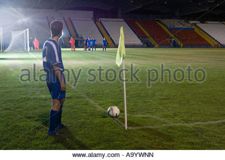 Footballer taking a corner kick - Stock Photo