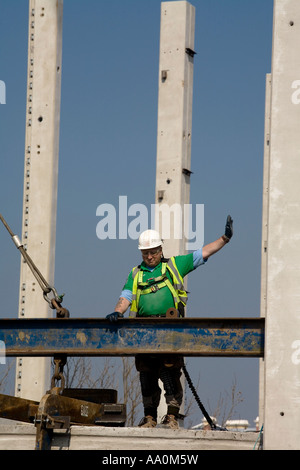 Construction worker wearing safety harness hard hat high vis hard hat and gloves giving directions on top of site - Stock Photo