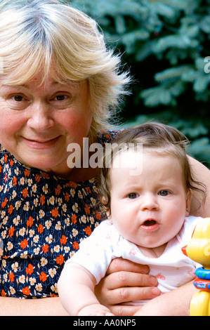 Poland, Mature woman holding granddaughter (6-9 months) in garden, portrait, close-up - Stock Photo