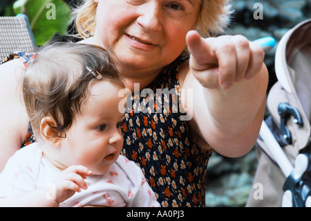 Poland, mature woman sitting with granddaughter (6-9 months) in garden, close-up, portrait - Stock Photo